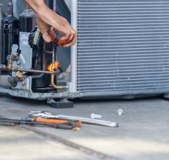 guys hands fixing outdoor ac unit